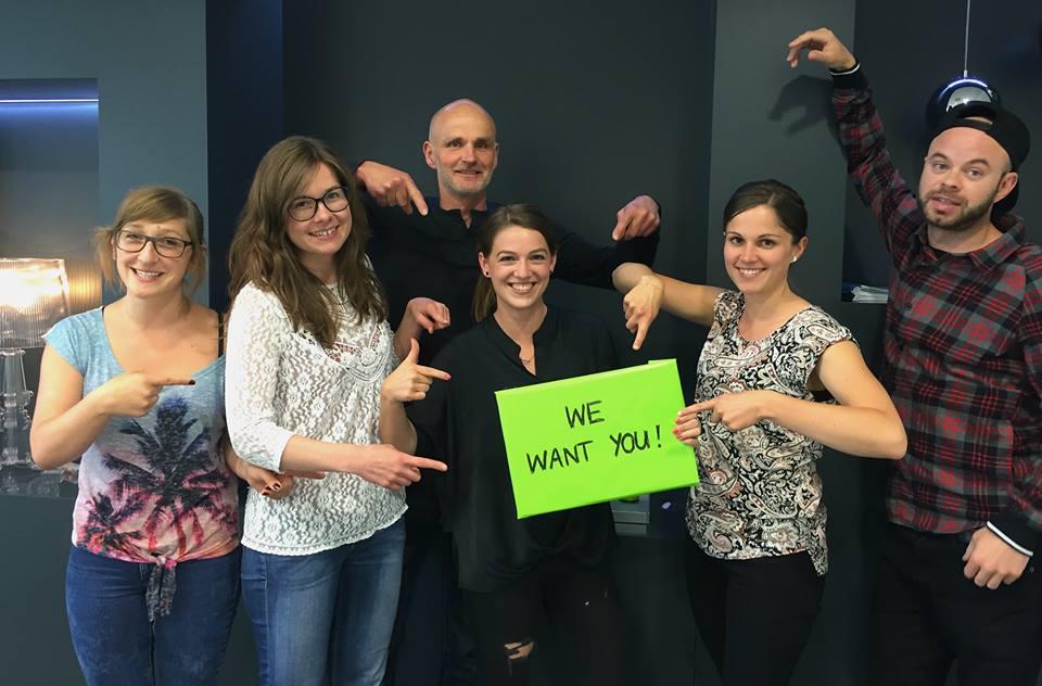 PR Job - Junges Team zeigt auf we want you Schild
