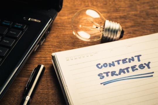 b2b content Strategie entwickeln Notizblock Schreibtisch Glühbirne Kreativität Notebook Stift Arbeitsplatz Schreibtisch