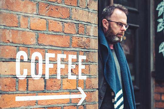 Kennzeichnung Influencer Beiträge Coffee Pfeil Hinweis Mann Mauer Backsteinwand